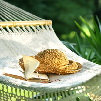 book, glasses and a straw hat lying on a hammock